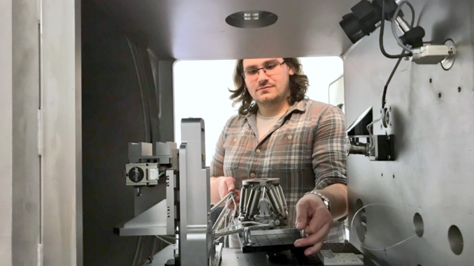 Dr. Glen Smales placing the hexapod in the sample chamber.